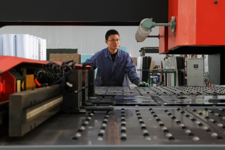 manufacturers: Luannan, November 24, 2012  A worker was operating CNC machine tools, in the DingRe Solar Energy Ltd, in November 24, 2012, Luannan County, china  The DingRe Solar Energy Ltd is the largest solar energy equipment manufacturers in Hebei province