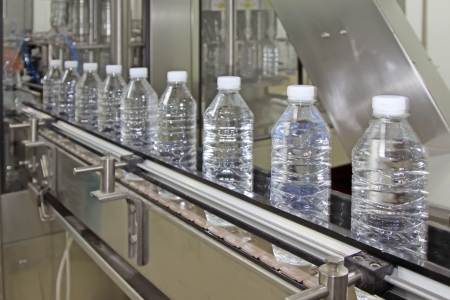 standardization: bottled mineral water production line in a factory Stock Photo