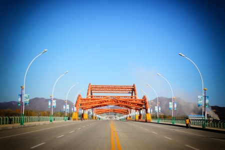 capacious: road through the bridge with blue sky background of a city, north china