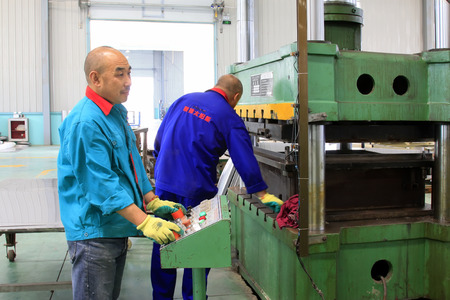 punch press: TANGSHAN CITY - MAY 29: Workers operating hydraulic press processing products in a factory, on may 29, 2014, Tangshan city, Hebei Province, China  Editorial