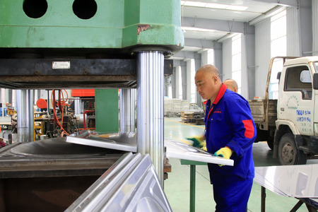 TANGSHAN CITY - MAY 29: Workers operating hydraulic press processing products in a factory, on may 29, 2014, Tangshan city, Hebei Province, China
