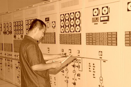 parameters: LUANNAN COUNTY - AUGUST 26: A worker was recording instrument parameters in a transformer room of a factory, On August 26, 2011, luannan county, hebei province, china.