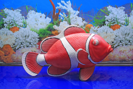 model fish: Red plastic model of fish in an aquarium, closeup of photo Stock Photo