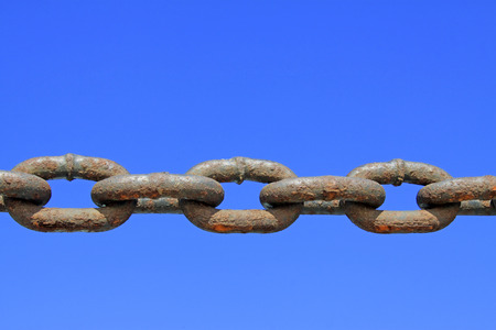 solid blue background: oxidation rusty chains under the blue sky, closeup of photo Stock Photo