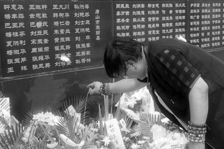 sacrifices: Tangshan City, July 28: A man Offering sacrifices to their loved ones died in the earthquake, before the Tangshan Earthquake Memorial Wall on July 28, 2012, Tangshan City, Hebei Province, China.