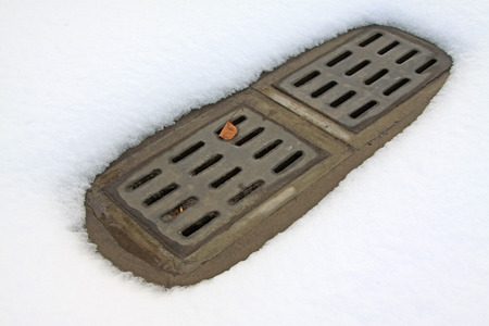 sewer: Sewer mouth and snow, closeup of photo