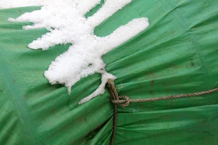 chaining: Green tent in the snow, closeup of photo Stock Photo