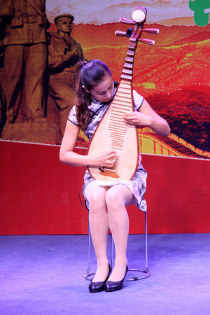 pipa: TANGSHAN CITY - AUGUST 15: A woman playing pipa at the party on August 15, 2015, Tangshan City, Hebei Province, China