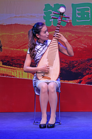 tangshan city: TANGSHAN CITY - AUGUST 15: A woman playing pipa at the party on August 15, 2015, Tangshan City, Hebei Province, China
