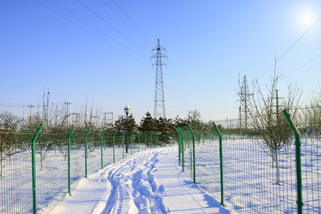 dazzle: metal fences and electric power tower in the snow, closeup of photo