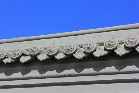 inner wear: Gray eaves tiles on the wall in a temple, closeup of photo Stock Photo