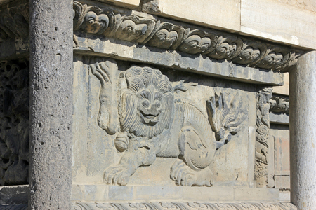 abrasion: lion sculptures in grey wall, closeup of photo
