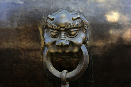 commemorate: beast head on Chinese style copper urn in a temple, closeup of photo