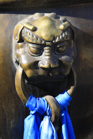 mouth cloth: beast face on a copper tank, closeup of photo