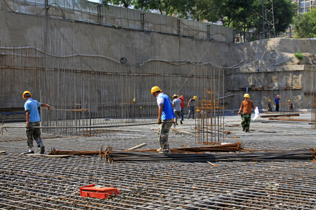 Luannan County - August 21: construction workers handling reinforced bar in the construction site, on August 21, 2015, luannan county, hebei province, China