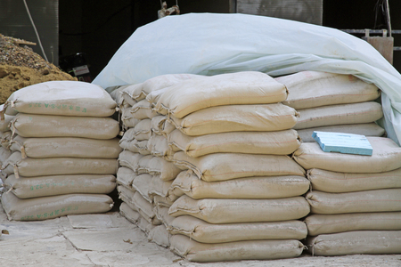 construction material: Bagged cement in the construction site, closeup of photo