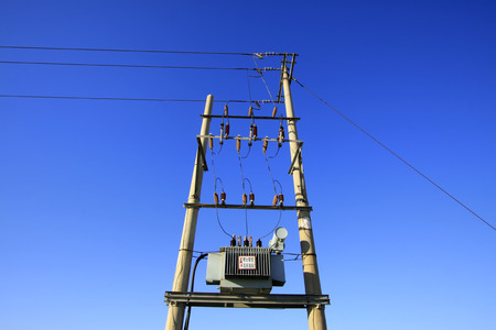 solid wire: Transformer and pole under the blue sky, closeup of photo