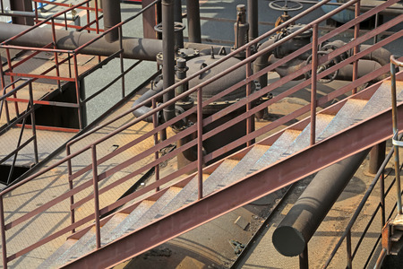 oxidize: oxidize pipeline and stairs in a factory, closeup of photo