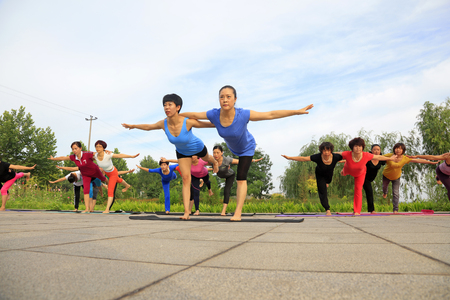 physique: Tangshan - July 3 2016: women doing yoga exercise in the park, tangshan city, hebei province, China