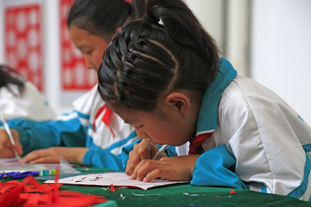 auspicious element: Luannan county - May 13: primary school students producting paper-cut works, on May 13, 2016, Luannan county, hebei province, China.