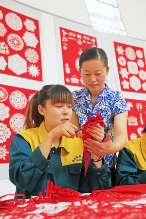 auspicious element: Luannan county - May 13: Teachers guiding students paper-cut works, on May 13, 2016, Luannan county, hebei province, China. Editorial