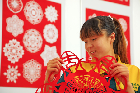 Luannan county - May 13: a girl watching paper-cut works, on May 13, 2016, Luannan county, hebei province, China. Editorial