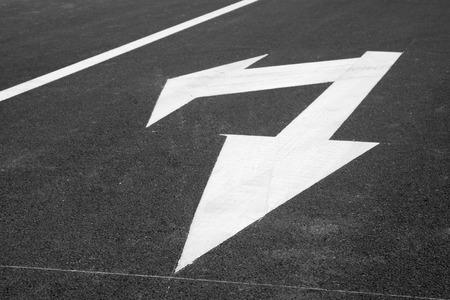 turn down: Turn down arrow on the asphalt road, closeup of photo Stock Photo