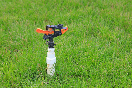sprinkler irrigation equipment in lawn Stock Photo