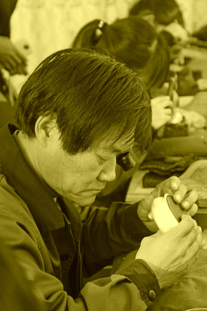 art processing: TANGSHAN CITY - NOVEMBER 18: Workers processing gold and silver handicrafts in a factory, on november 18, 2014, Tangshan City, Hebei Province, China