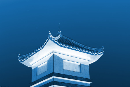 Chinese architectural style tower under blue sky, closeup of photo