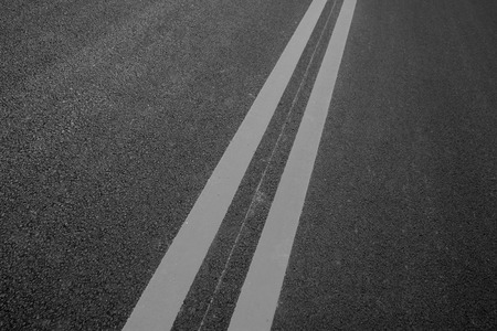 Double yellow lines on the asphalt road, closeup of photo 版權商用圖片