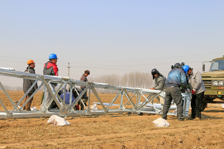onsite: Tangshan City - March 1, 2016: Power workers were installing pylons in the field, Tangshan City, Hebei, China, March 1st, 2016
