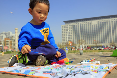 hebei: Luannan County - April 15, 2017: little boy painting on a kite, Luannan County, Hebei Province, China, April 15, 2017