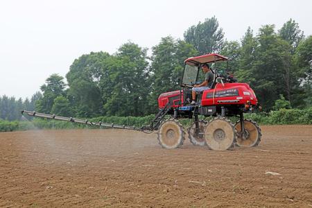 Luannan County - August 11, 2017: self-propelled boom sprayer working on a farm, Luannan, Hebei, China