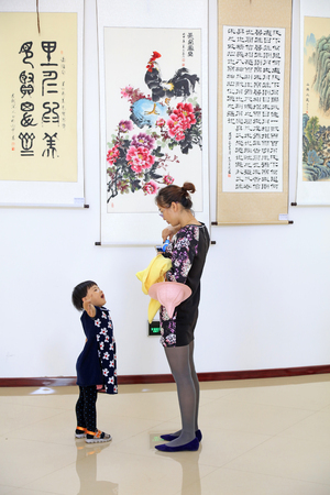 Tangshan City - May 13, 2016: mother and daughter two people enjoy painting and calligraphy works indoors, Tangshan City, Hebei, China