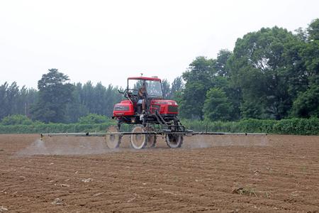 Luannan County - August 11, 2017: self-propelled boom sprayer working on a farm, Luannan, Hebei, China Редакционное