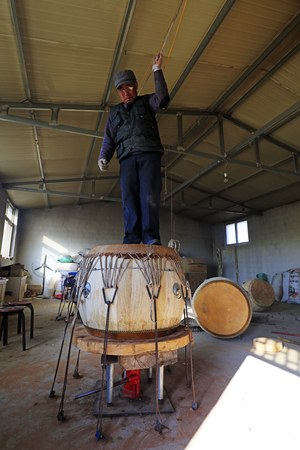 Luannan County - February 6, 2018: craftsman is treading drumhead in workshops, Luannan, Hebei, China