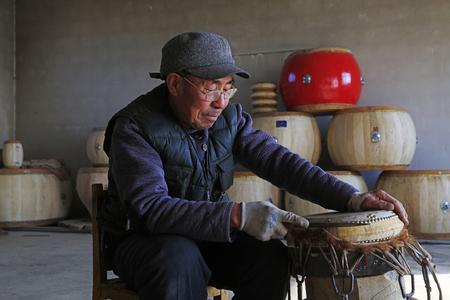 Luannan County - February 6, 2018: craftsman is working on the drum in workshops, Luannan, Hebei, China Redakční