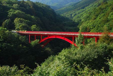 Red steel bridge in mountain photo
