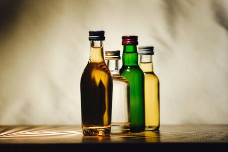 different alcohol bottles are on the table on a light background.