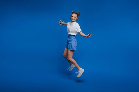 full-size portrait of an excited surprised attractive inspired girl Bouncing in isolation on a blue background.