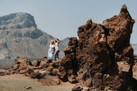 a guy and a girl in white clothes and glasses stand in the crater of the El Teide volcano, a Couple stands on a mountain in the crater of a volcano on the island of Tenerife, Spain
