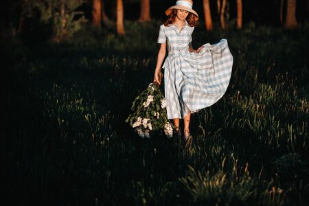 Beautiful girl enjoying the smell of lilac on a summer day. Aromatherapy and spring concept. A pretty girl, a beautiful woman in a blue long vintage dress is standing in a lilac garden. Gardening.