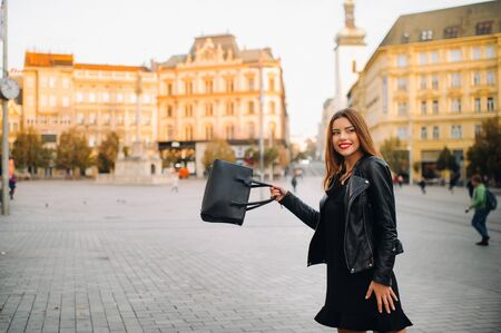 A young beautiful stylish girl in a black summer dress and jacket and with a purse walks through the old city.Girl-model in the Czech Republic. BRNO. Stock Photo