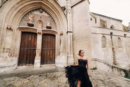 A stylish bride in a black wedding dress poses in the old French city of Avignon. Model in a black dress. The papal Palace in Avignon, Provence