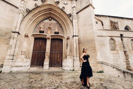A stylish bride in a black wedding dress poses in the ancient French city of Avignon. Model in a beautiful black dress. Photo shoot in Provence Imagens