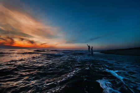 A couple in love at sunset on the background of the sea, an unrecognizable couple Portrait of a beautiful newlywed couple expecting a child. Photo