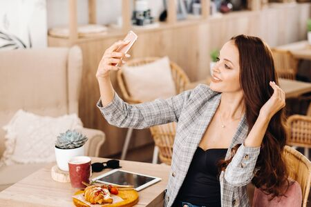 a business Girl is sitting in a cafe and taking a selfie,a Girl in a coffee shop is smiling and taking a selfie on a smartphone.