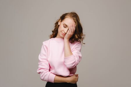 a girl with long hair on a gray background suffering from a headache holds her head with her hands. The girl puts her hands on her head, isolated against a gray background. The concept of problems and headaches Stock fotó