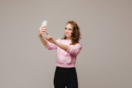 A smiling happy girl in a pink blouse takes a selfie on a smartphone on a gray background 版權商用圖片